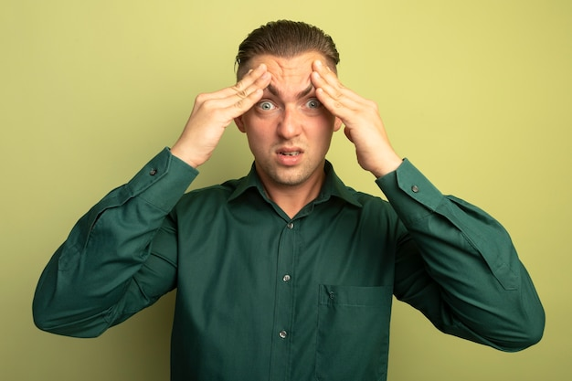 그의 이마에 손으로 정면을보고 녹색 셔츠에 젊은 잘 생긴 남자가 혼란스럽고 가벼운 벽 위에 서서 짜증을 낸다.
