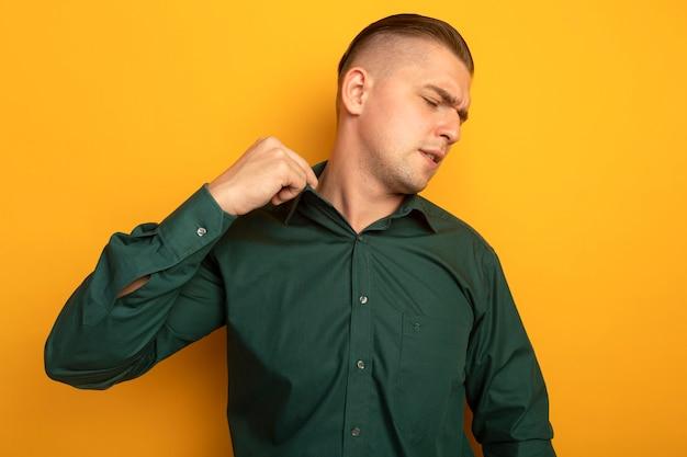 혼란스럽고 불쾌한 녹색 셔츠에 젊은 잘 생긴 남자가 주황색 벽 위에 서있는 그의 칼라를 고정