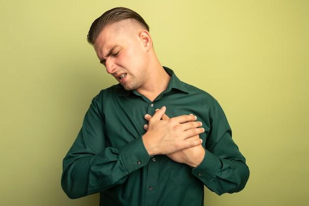 녹색 셔츠에 젊은 잘 생긴 남자가 가벼운 벽 위에 서있는 고통을 느끼는 그의 가슴에 손을 잡고 몸이 좋지 않습니다.