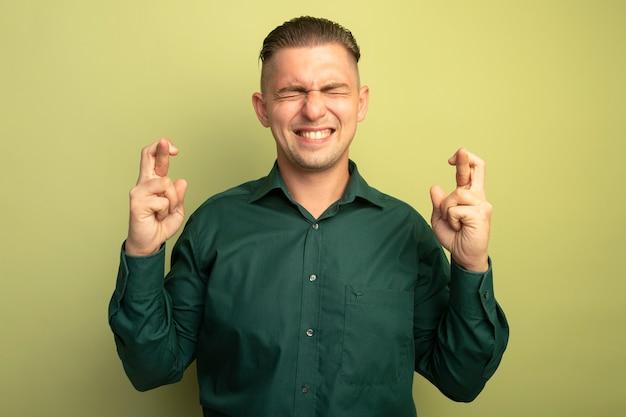 밝은 벽 위에 서있는 희망 표현으로 손가락을 건너는 닫힌 눈으로 바람직한 소원을 만드는 녹색 셔츠에 젊은 잘 생긴 남자