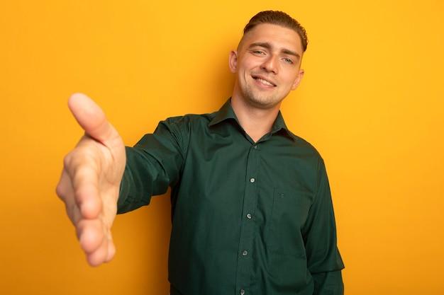 Молодой красавец в зеленой рубашке, предлагая руку приветствовать дружелюбно улыбаясь