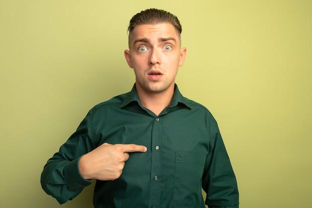 자신을 가리키는 녹색 셔츠에 젊은 잘 생긴 남자가 빛 벽에 서 혼란스러워