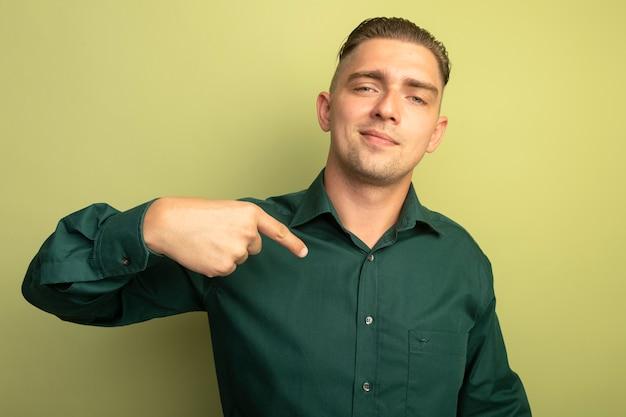 빛 벽 위에 자신감 서 찾고 자신을 손가락으로 가리키는 녹색 셔츠에 젊은 잘 생긴 남자