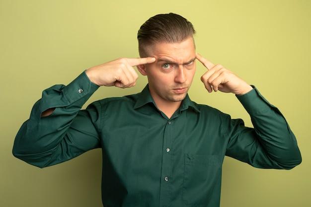 가벼운 벽 위에 서있는 심각한 얼굴로 정면을보고 사원에서 idex 손가락으로 가리키는 녹색 셔츠에 젊은 잘 생긴 남자