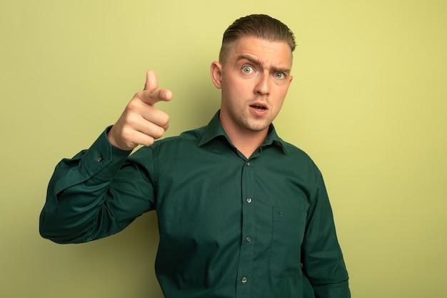 카메라에서 검지 손가락으로 가리키는 녹색 셔츠에 젊은 잘 생긴 남자가 빛 벽 위에 서 혼란스러워