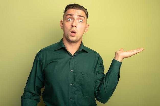 녹색 셔츠에 젊은 잘 생긴 남자 미친 찾고 뭔가를 제시하고 빛 벽 위에 서 놀란