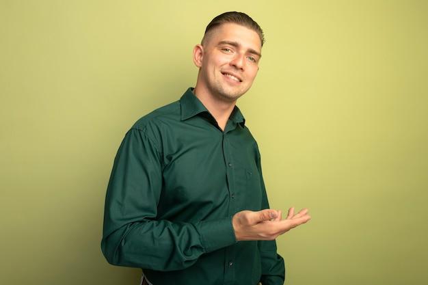웃는 그의 손의 팔로 뭔가를 제시하는 녹색 셔츠에 젊은 잘 생긴 남자
