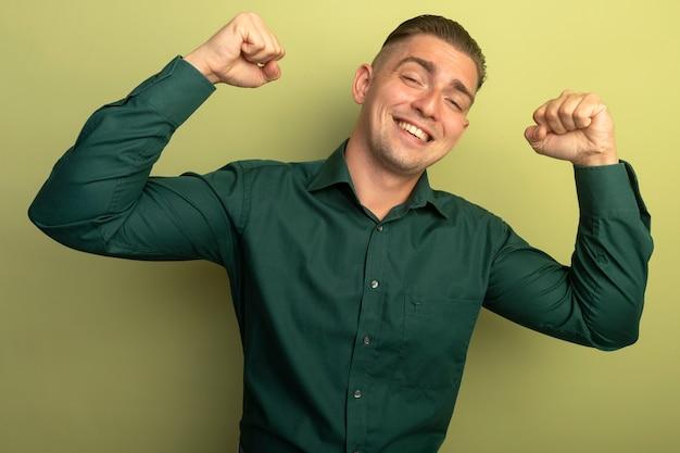 밝은 벽에 서 행복하고 긍정적 인 승자 개념 주먹을 올리는 녹색 셔츠에 젊은 잘 생긴 남자