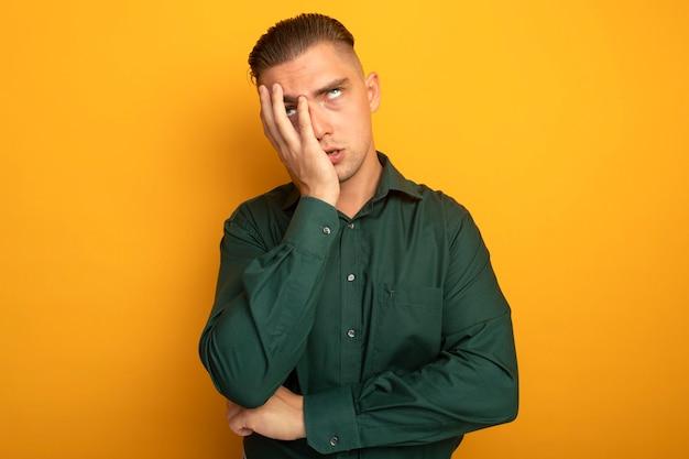 녹색 셔츠에 젊은 잘 생긴 남자 눈을 감고 피곤하고 귀찮게