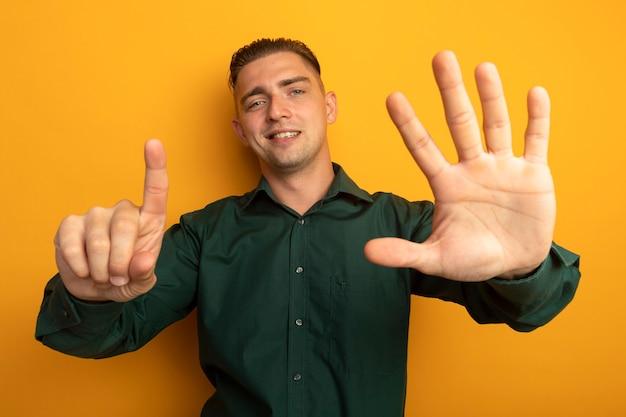 녹색 셔츠를 보여주는 젊은 잘 생긴 남자가 유쾌하게 웃고있는 6 번 손가락으로 가리키는