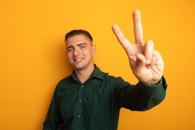 Молодой красавец в зеленой рубашке весело улыбается, показывая v-знак счастливым и позитивным