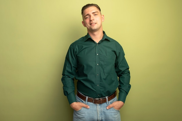 緑のシャツを着た若いハンサムな男は、ポケットに手を握って自信を持って笑っています。