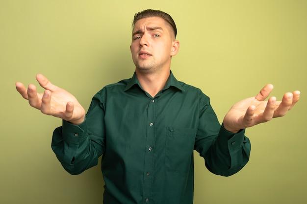 가벼운 벽 위에 서있는 녹색 셔츠에 잘 생긴 젊은이