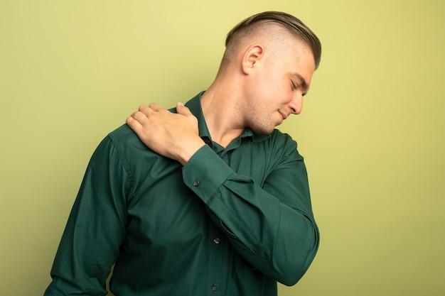 明るい壁の上に立っている痛みを感じて彼の肩に触れている緑のシャツの若いハンサムな男