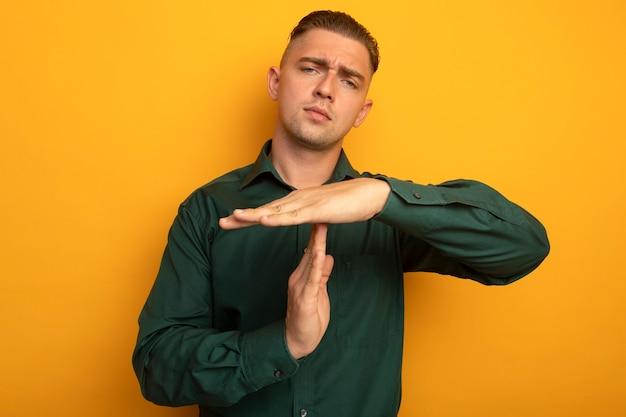 Молодой красавец в зеленой рубашке с серьезным лицом делает тайм-аут руками