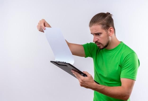 Молодой красавец в зеленой футболке держит буфер обмена, глядя на бланк бумаги, удивлен и смущен, стоя на белом фоне