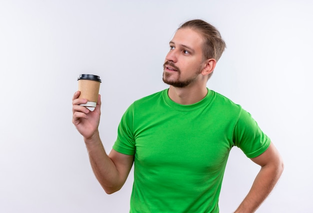 白い背景の上に立っている顔に自信を持って式とよそ見コーヒーカップを保持している緑のtシャツの若いハンサムな男