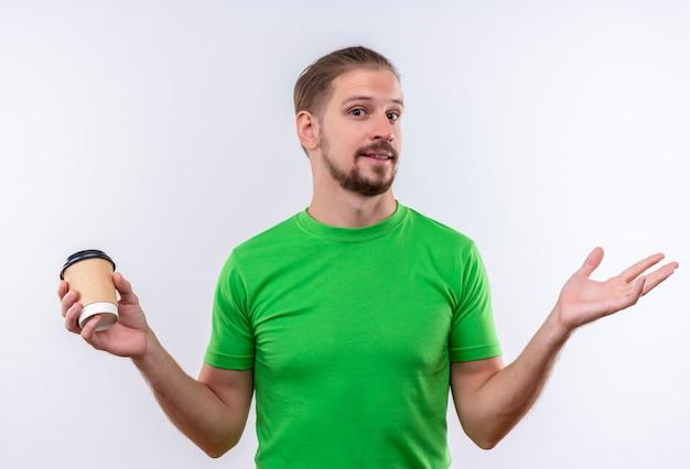 Молодой красивый мужчина в зеленой футболке держит чашку кофе, глядя в камеру, раздвигая руки, улыбаясь, стоя на белом фоне