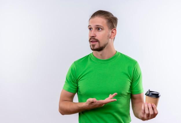 Молодой красавец в зеленой футболке держит чашку кофе в замешательстве, стоя на белом фоне