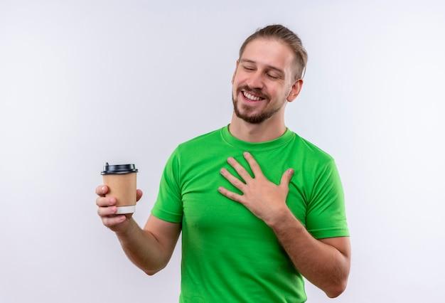 白い背景の上に元気に立って笑顔のコーヒーカップを保持している緑のtシャツの若いハンサムな男