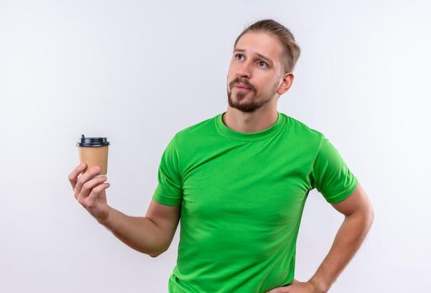 白い背景の上に立って不機嫌なコーヒーのカップを保持している緑のtシャツの若いハンサムな男
