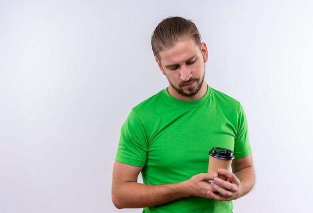 白い背景の上に立っている深刻な顔でそれを見てコーヒーのカップを保持している緑のtシャツの若いハンサムな男