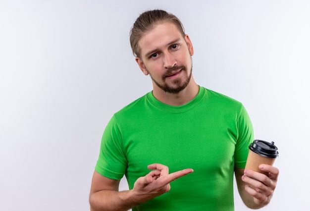 白い背景の上に自信を持って立っている探しているそれを指で指しているコーヒーのカップを保持している緑のtシャツの若いハンサムな男