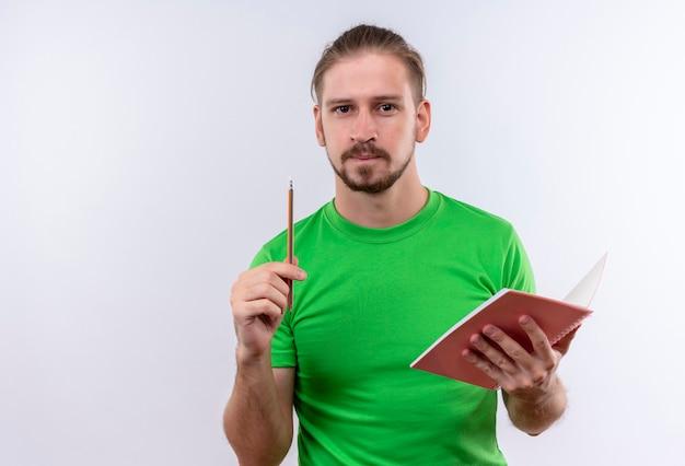 白い背景の上に立っている素晴らしいアイデアを持っていることを鉛筆で指しているノートを保持している緑のtシャツの若いハンサムな男