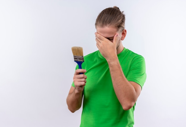 白い背景の上に立っている彼の手で顔を覆っているペイントブラシを保持している緑のtシャツの若いハンサムな男