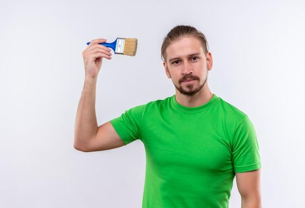 흰색 배경 위에 자신감 서 찾고 페인트 브러시를 들고 녹색 티셔츠에 젊은 잘 생긴 남자