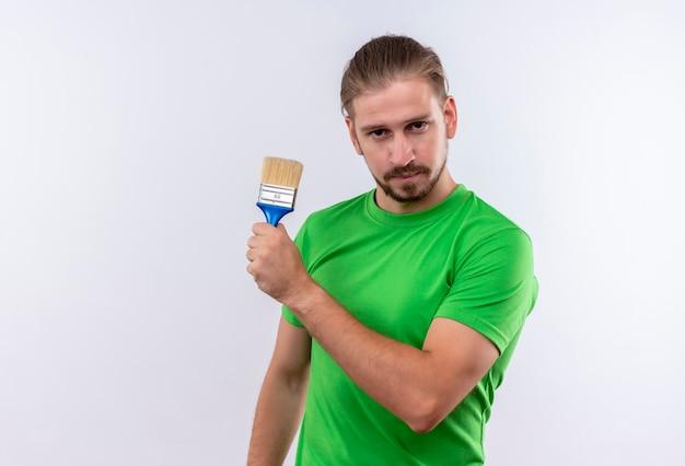 白い背景の上に自信を持って立っている探しているペイントブラシを保持している緑のtシャツの若いハンサムな男