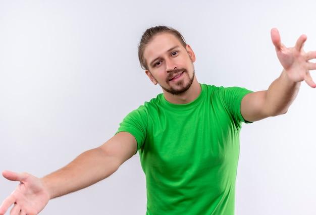 白い背景の上に立っている抱擁のための彼の武装を広くカメラの肯定的で幸せなオープニングで緑のtシャツを探している若いハンサムな男