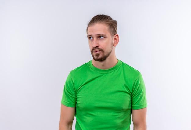 Молодой красавец в зеленой футболке смотрит в сторону недовольным и смущенным, стоя на белом фоне