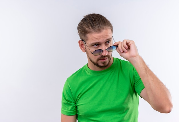 흰색 배경 위에 서있는 얼굴에 자신감이 표정으로 그의 안경을 벗고 옆으로 찾고 녹색 티셔츠에 젊은 잘 생긴 남자