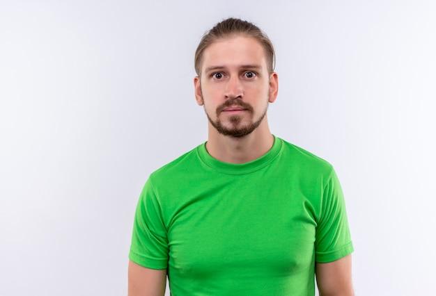 白い背景の上に驚いて、困惑して立っているカメラを見て緑のtシャツの若いハンサムな男