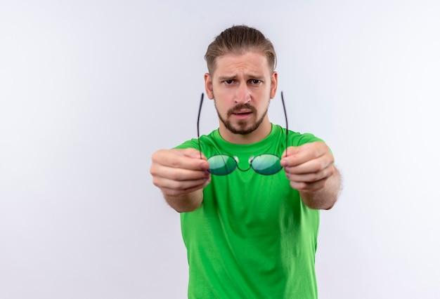 白い背景の上に立っている眼鏡を伸ばして自信を持って式でカメラを見て緑のtシャツの若いハンサムな男
