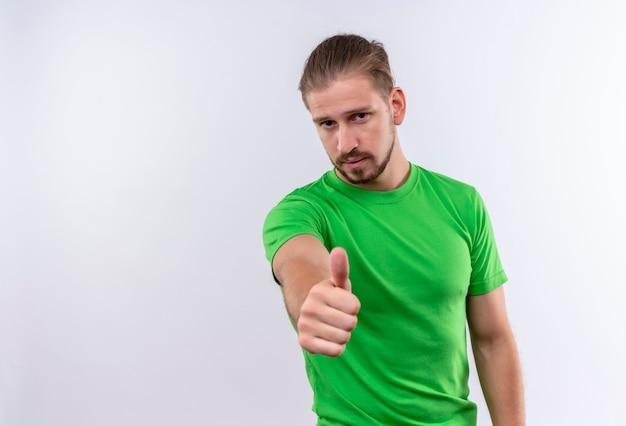 白い背景の上に立ってカメラの親指に自信を持って表示を探している緑のtシャツの若いハンサムな男