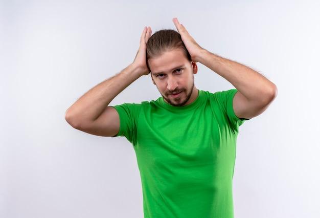 白い背景の上に立っている彼の完璧な髪に触れて自信を持って探している緑のtシャツの若いハンサムな男