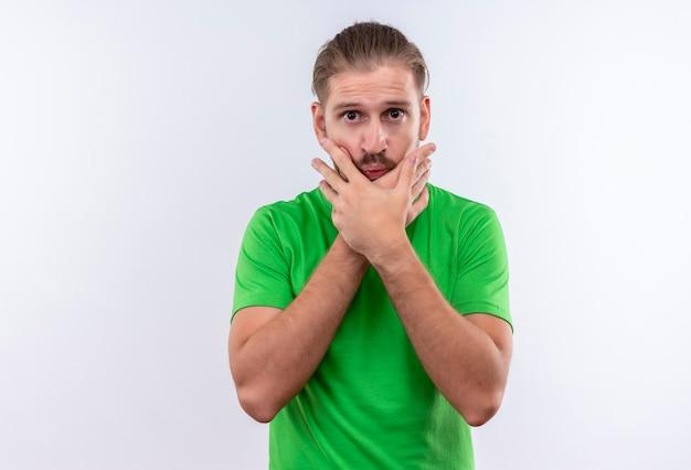 Молодой красивый мужчина в зеленой футболке выглядит смущенным и удивленным, держа лицо руками, стоящими на белом фоне