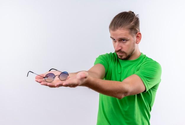 Молодой красавец в зеленой футболке предлагает кому-то свои очки, стоя на белом фоне