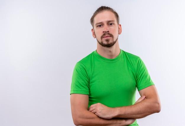 白い背景の上の深刻な顔でカメラを見て腕を組んで緑のtシャツ立っている若いハンサムな男