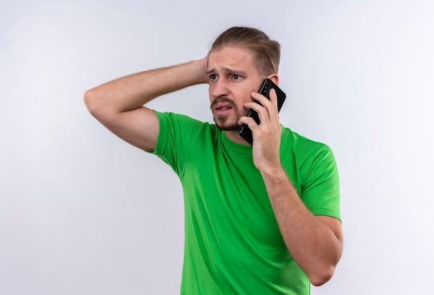 Молодой красавец в зеленой футболке разговаривает по мобильному телефону, выглядит смущенным и очень взволнованным, стоя на белом фоне