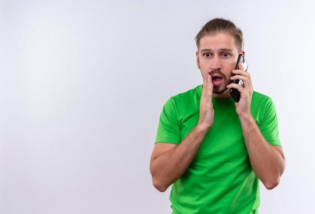 白い背景の上に驚いて、立って見て携帯電話で話している緑のtシャツの若いハンサムな男