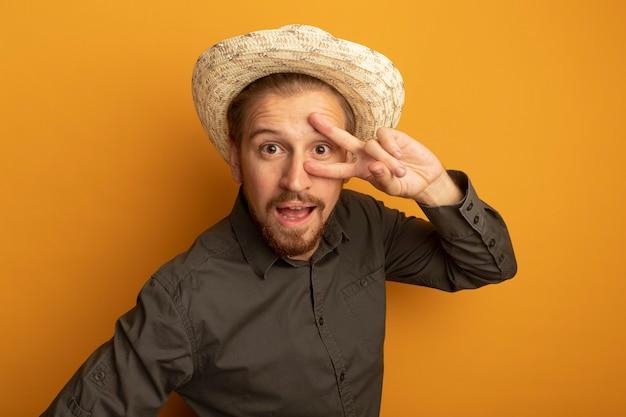 회색 셔츠와 여름 모자 행복하고 긍정적 인 v 기호를 보여주는 젊은 잘 생긴 남자