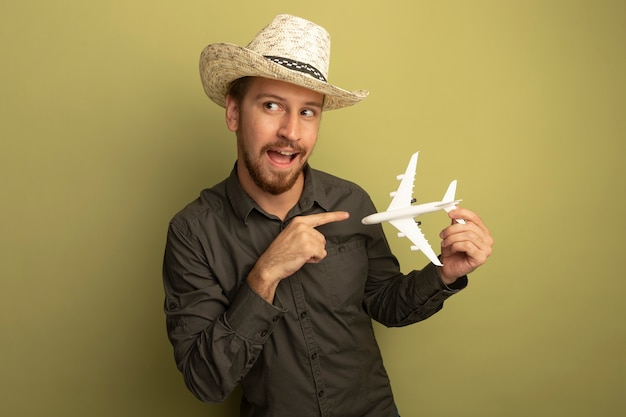 회색 셔츠와 여름 모자에 검지 손가락으로 행복하고 긍정적 인 장난감 비행기를 들고 젊은 잘 생긴 남자