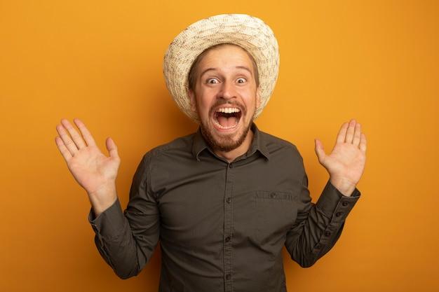 회색 셔츠와 여름 모자에 젊은 잘 생긴 남자가 카메라를보고 팔을 올려 미친 행복을 외치고