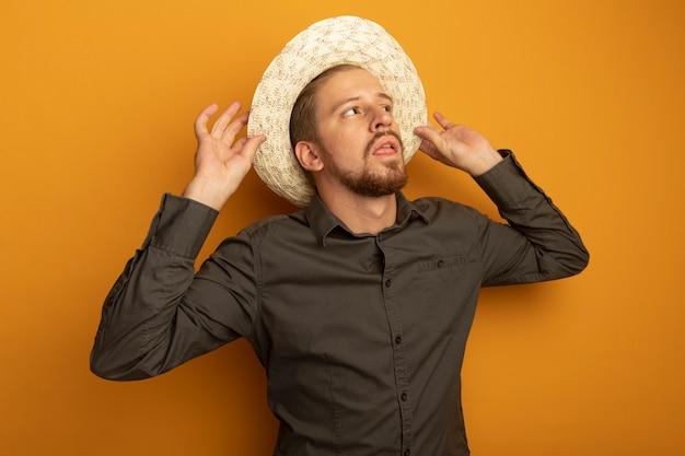 회색 셔츠와 여름 모자에 젊은 잘 생긴 남자가 자신감 표정으로 제쳐두고 찾고