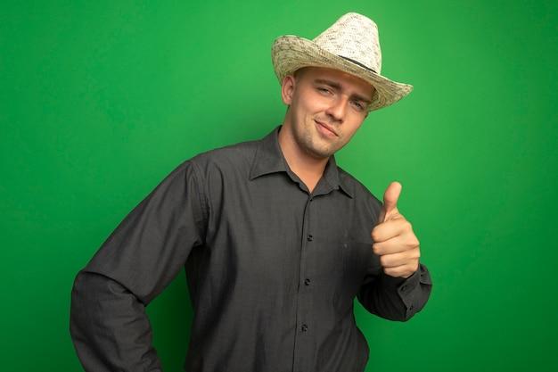 灰色のシャツと夏の帽子の若いハンサムな男が正面を見て、幸せそうな顔で笑って、緑の壁の上に立って親指を示しています