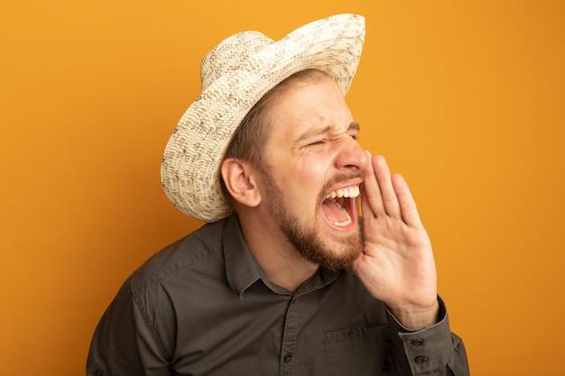 회색 셔츠와 여름 모자에 젊은 잘 생긴 남자가 소리를 지르거나 입 근처에서 손으로 누군가를 부르고 흥분하고 감정적입니다.