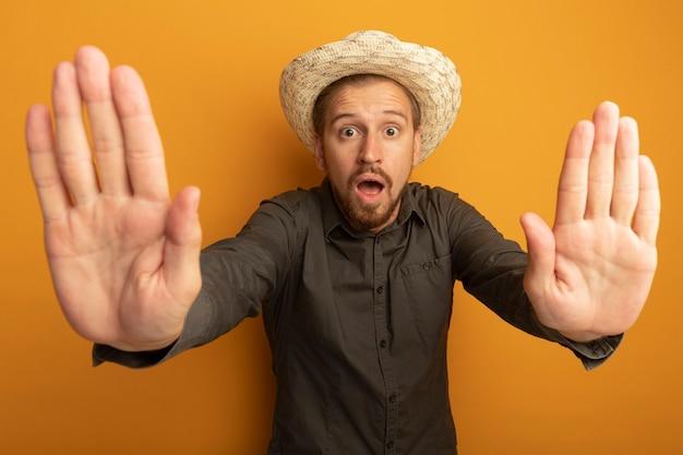 회색 셔츠와 여름 모자에 젊은 잘 생긴 남자는 두려움 표현이 열려 손으로 제스처를 중지와 걱정